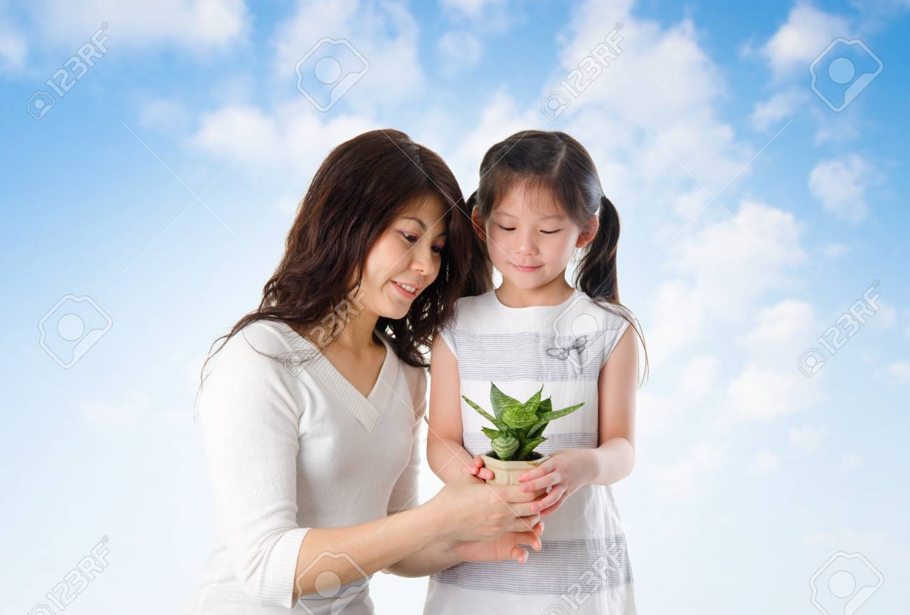 Happy Asian young mother with daughter taking care plant in summer day, blue sky as background. Stock Photo - 18494896
