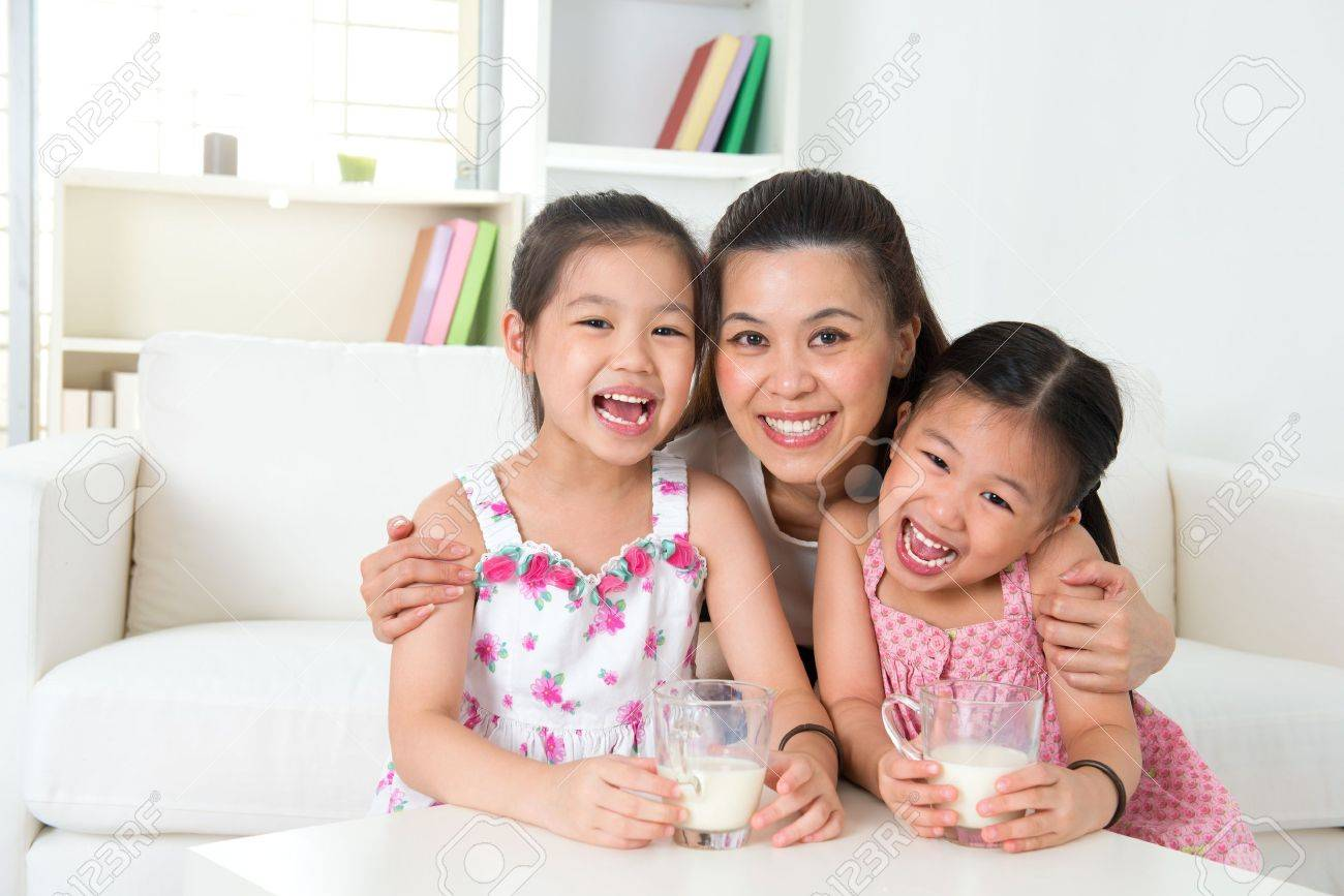Happy Asian mother and daughters drinking milk at home Stock Photo - 20150568