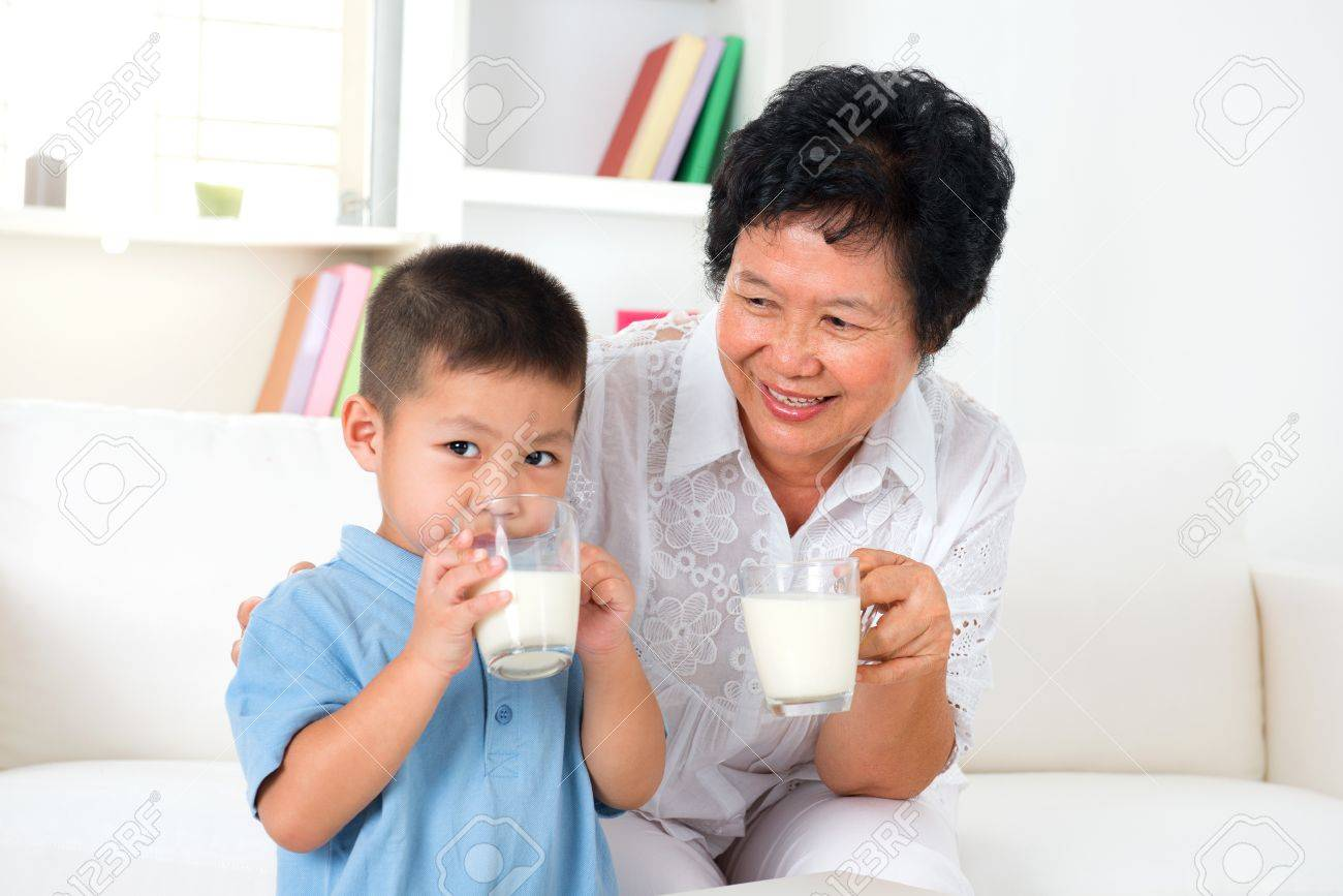 Beautiful grandmother and grandson drinking milk at home Stock Photo - 20150537