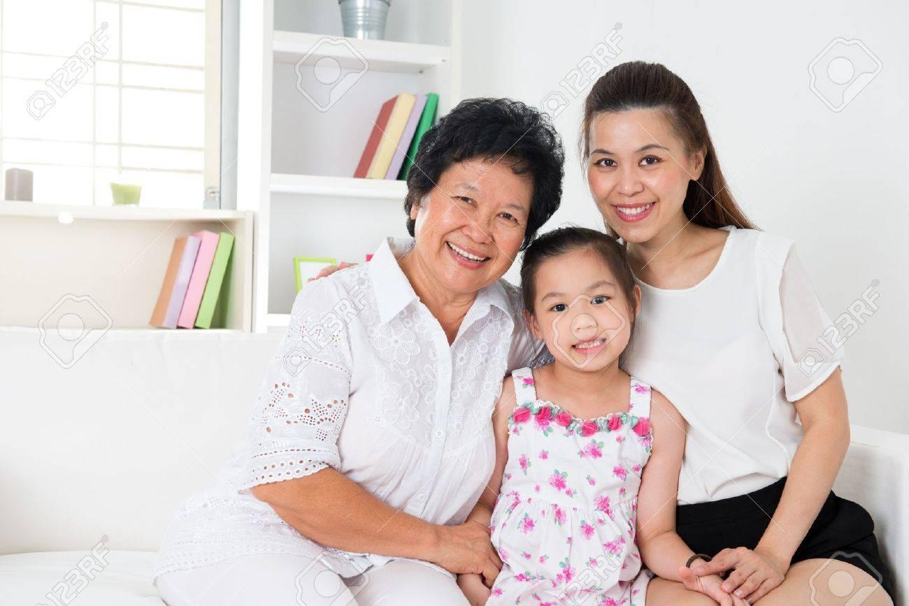 grandparent parent and grandchild sitting on sofa smiling stock