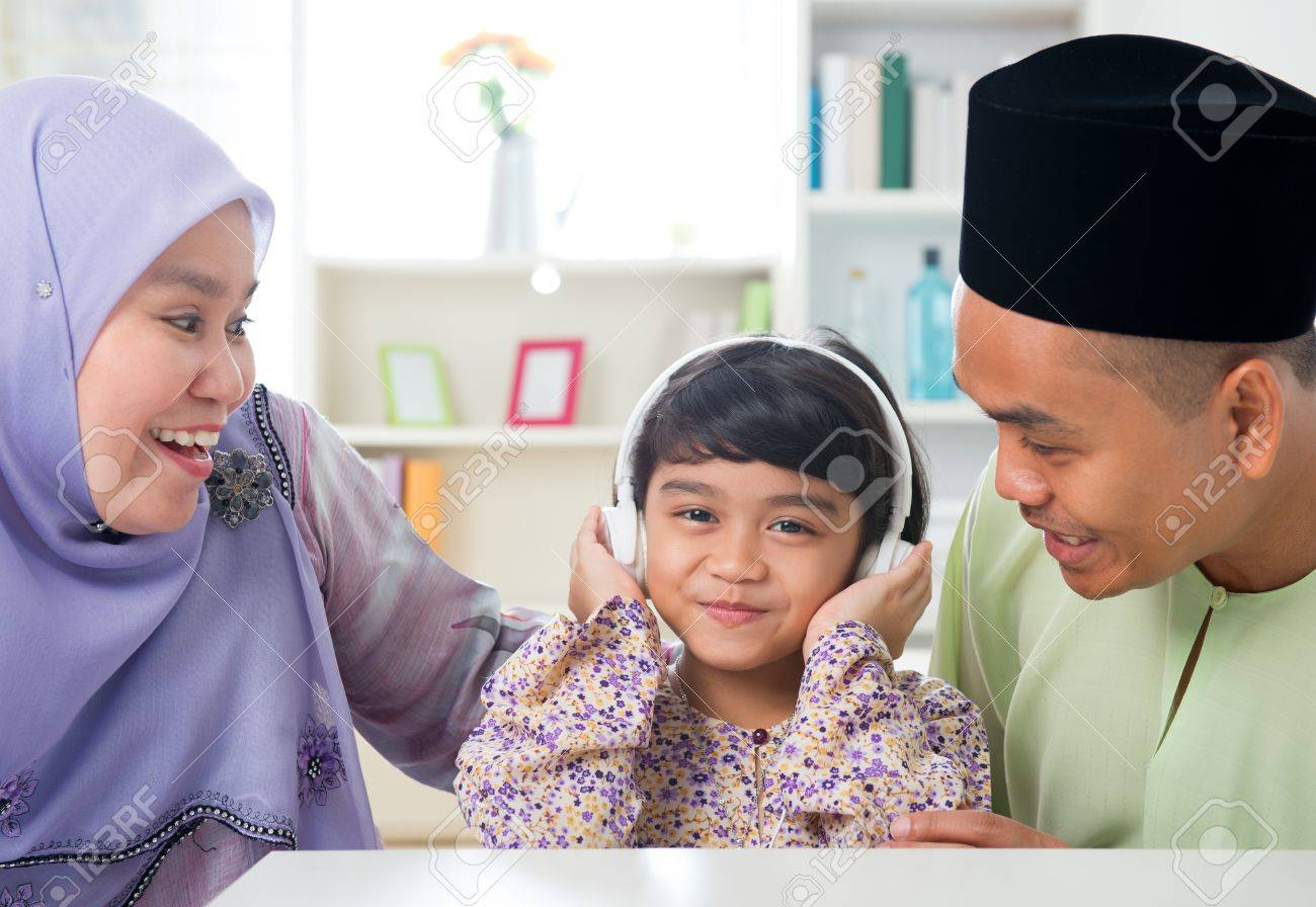 Muslim girl listening to music at home. Southeast Asian family living lifestyle. Happy smiling Malay parents and child. Stock Photo - 20434474