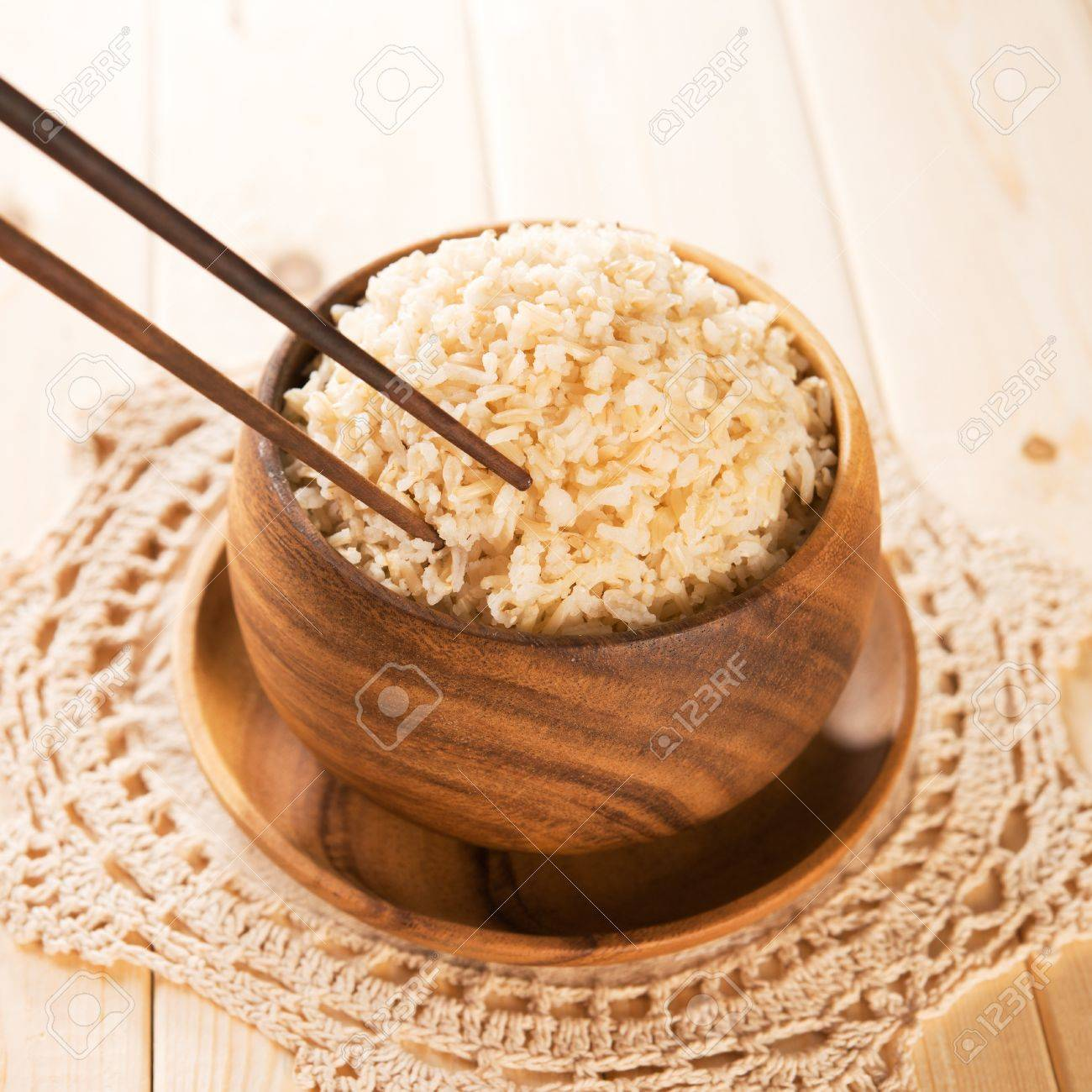 Close Up Cookedanic Basmati Brown Rice In Wooden Bowl With Chopsticks On  Dining Table