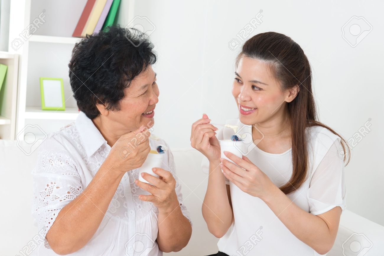 Eating yoghurt . Happy Asian family eating yogurt at home. Beautiful senior mother and adult daughter, healthcare concept. Stock Photo - 21412031