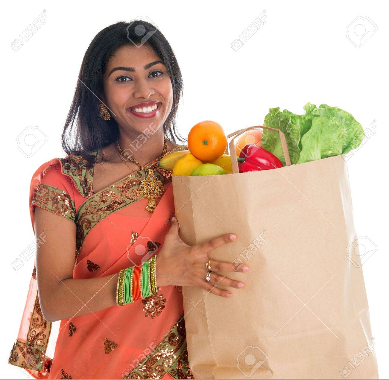Happy grocery shopper. Portrait of beautiful traditional Indian woman in sari dress holding paper shopping bag full of groceries isolated on white. Stock Photo - 21621308