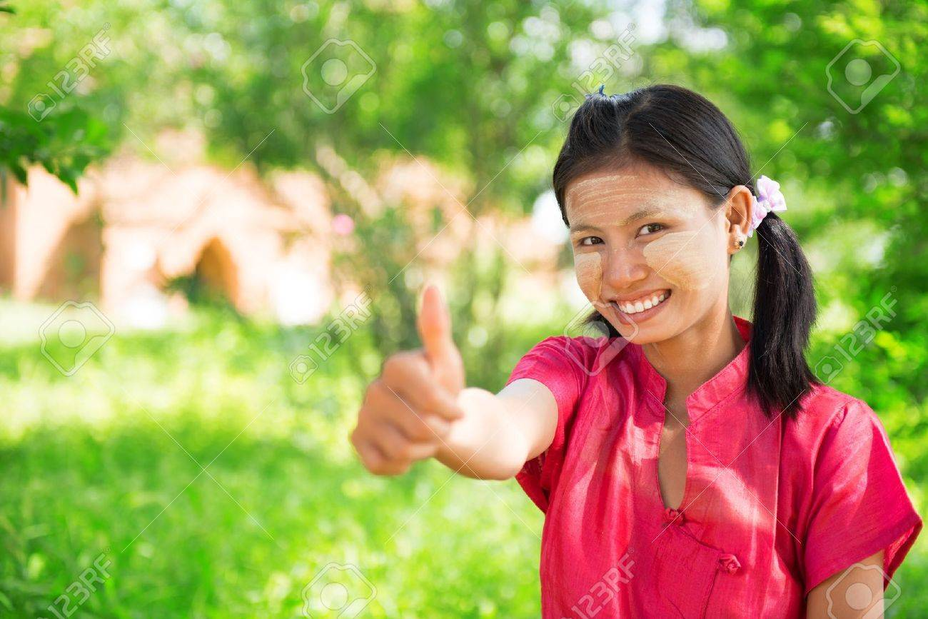 Portrait of happy smiling beautiful young traditional Myanmar girl thumb up at outdoor. Stock Photo - 22112480