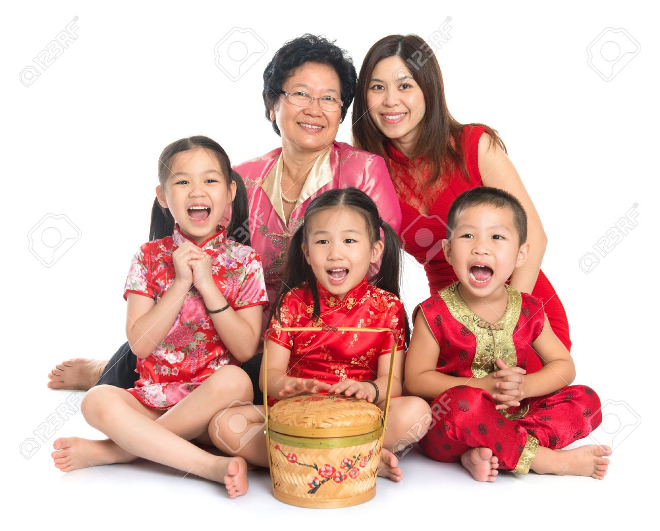 Group of happy multi generations Asian Chinese family wishing you a happy Chinese New Year, with traditional Cheongsam sitting isolated on white background. Stock Photo - 22284234