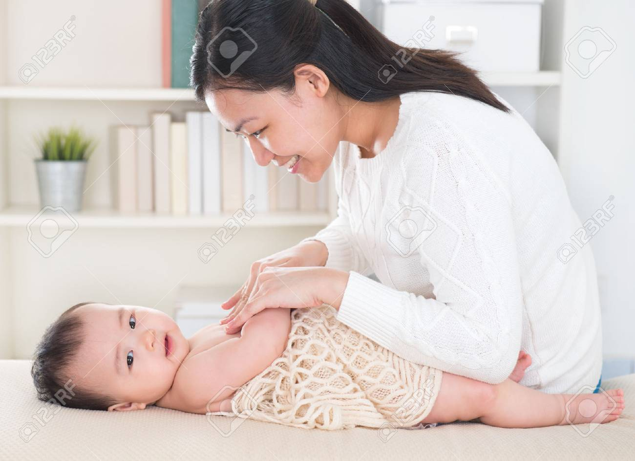 Asian mother giving massage to baby girl at home. Stock Photo - 22550871