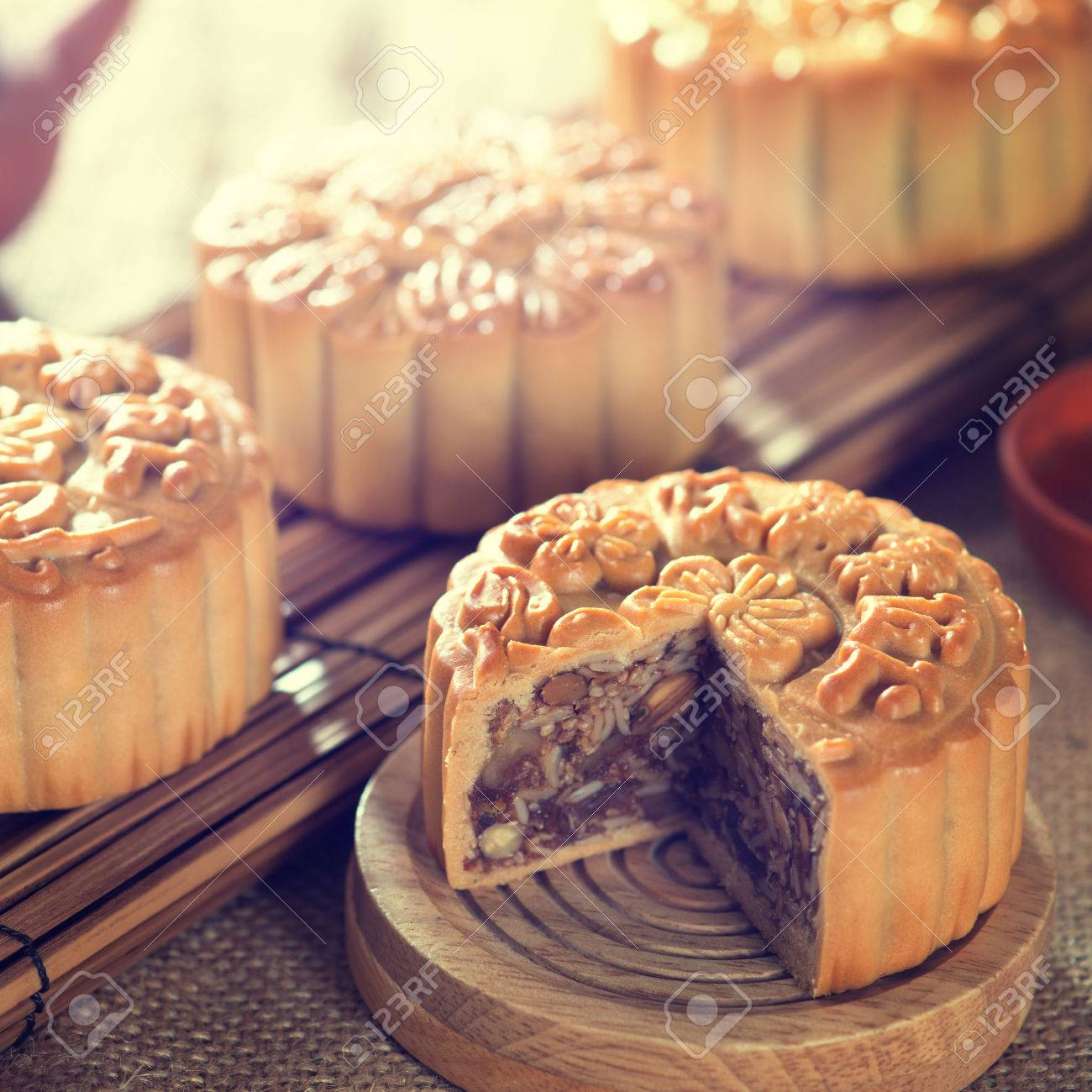 Retro vintage style Chinese mid autumn festival foods. Traditional mooncakes on table setting with teacup & Retro Vintage Style Chinese Mid Autumn Festival Foods. Traditional ...