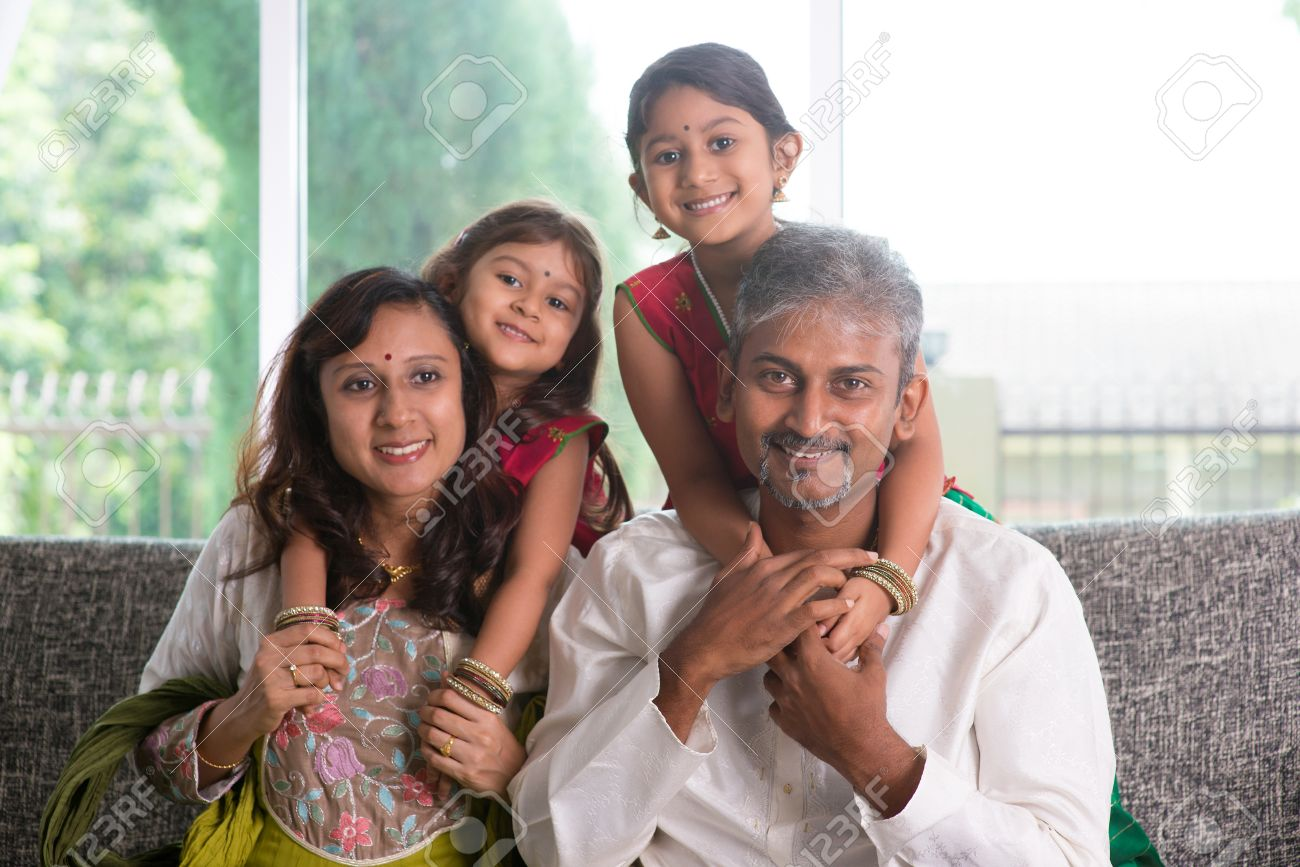 happy indian family at home asian parents piggyback their kids