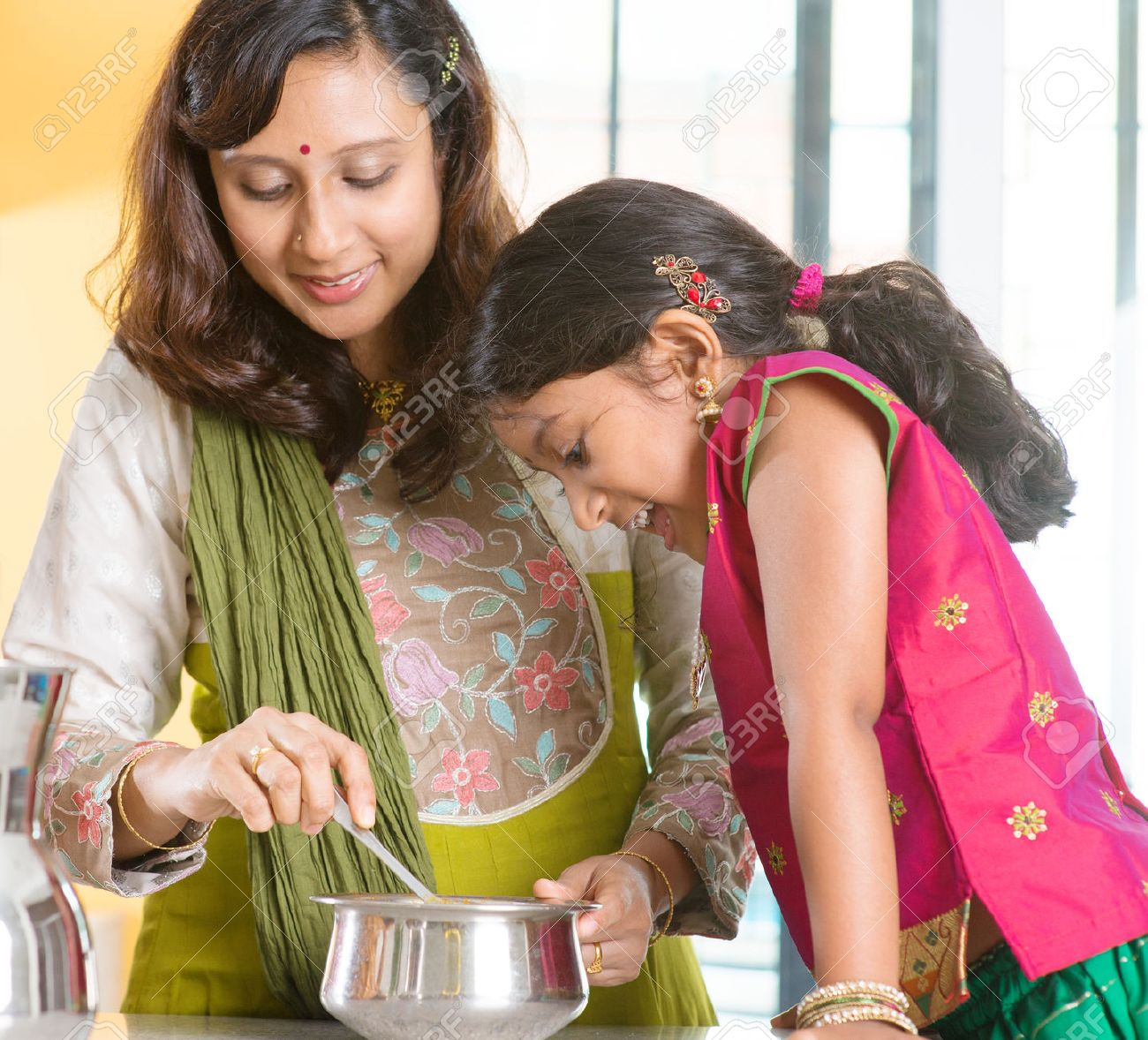 Asian family cooking food together at home  Indian mother and