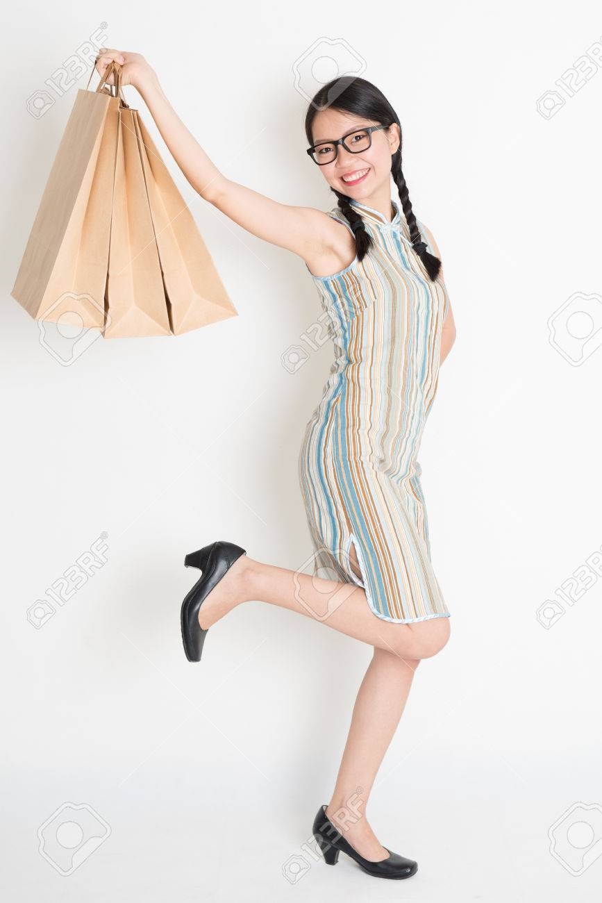 c621f2470106 Portrait of excited Asian Chinese woman hands holding paper shopping bags
