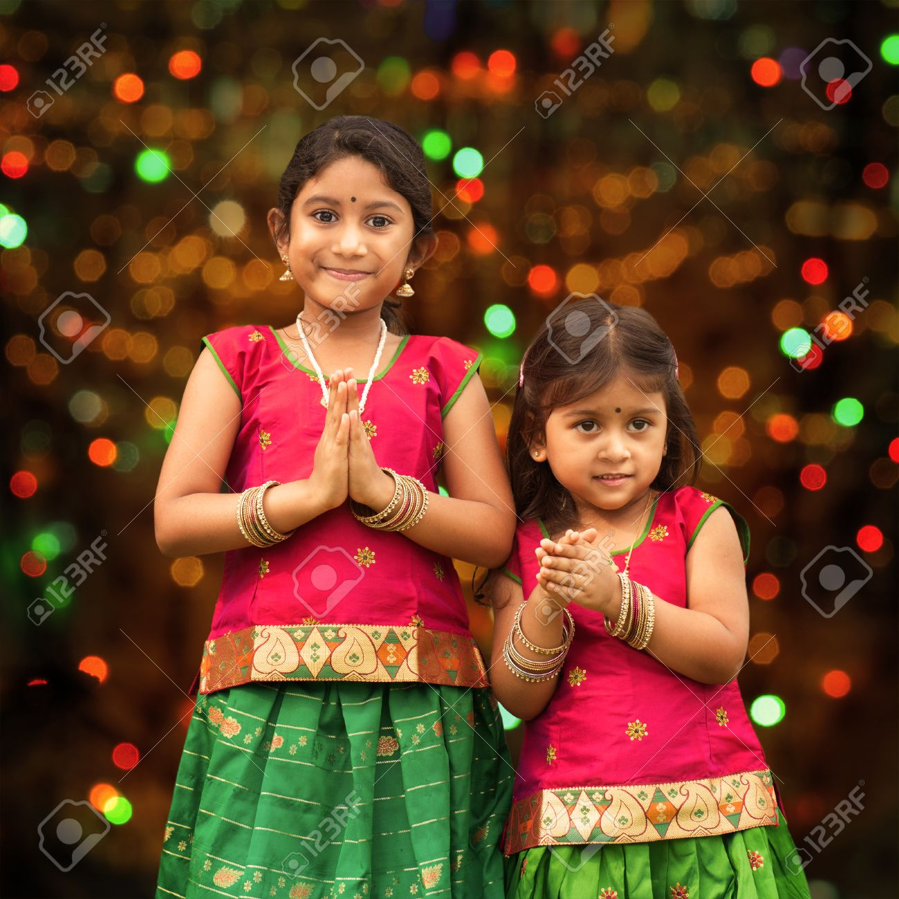 Cute Indian Girls Dressed In Sari With Folded Hands Representing