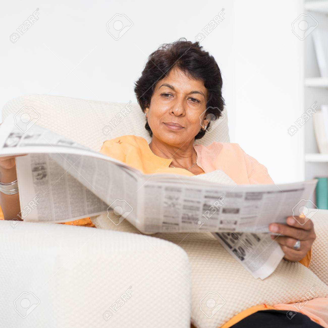 portrait of a 50s indian mature woman reading newspaper, sitting