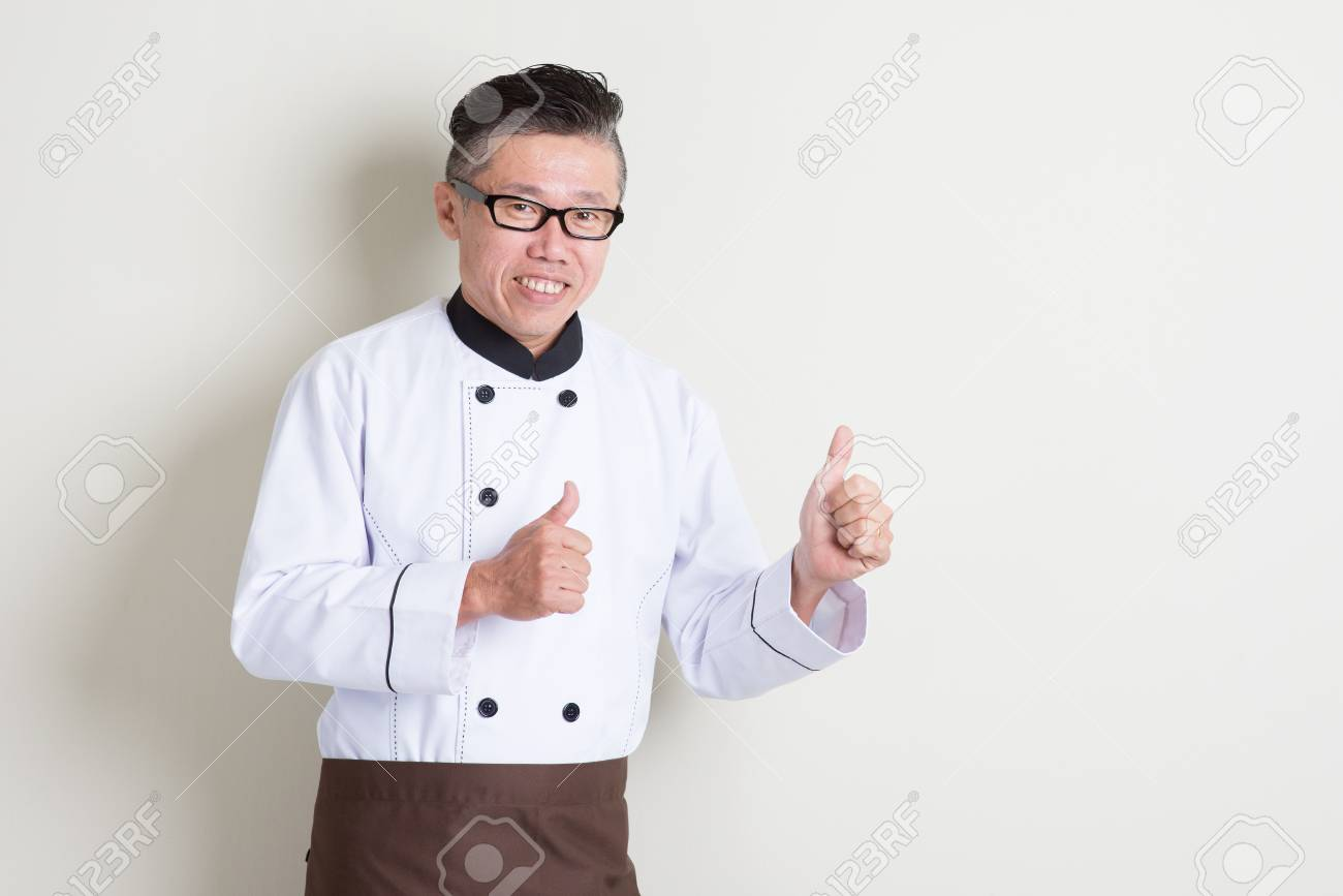 portrait of 50s mature asian male chef in uniform giving thumbs