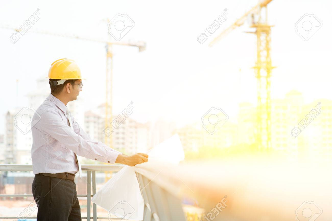 2b28d56ef7c Asian Indian male site contractor engineer with hard hat holding blue print  paper inspecting at construction