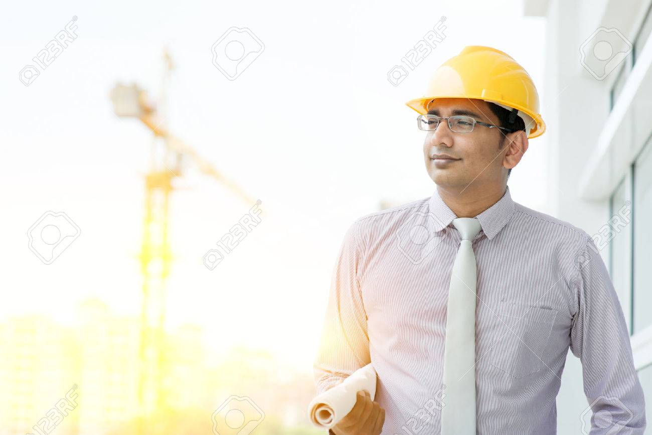 8af2e8e246d Handsome Asian Indian male site contractor engineer with hard hat holding  blue print paper walking at