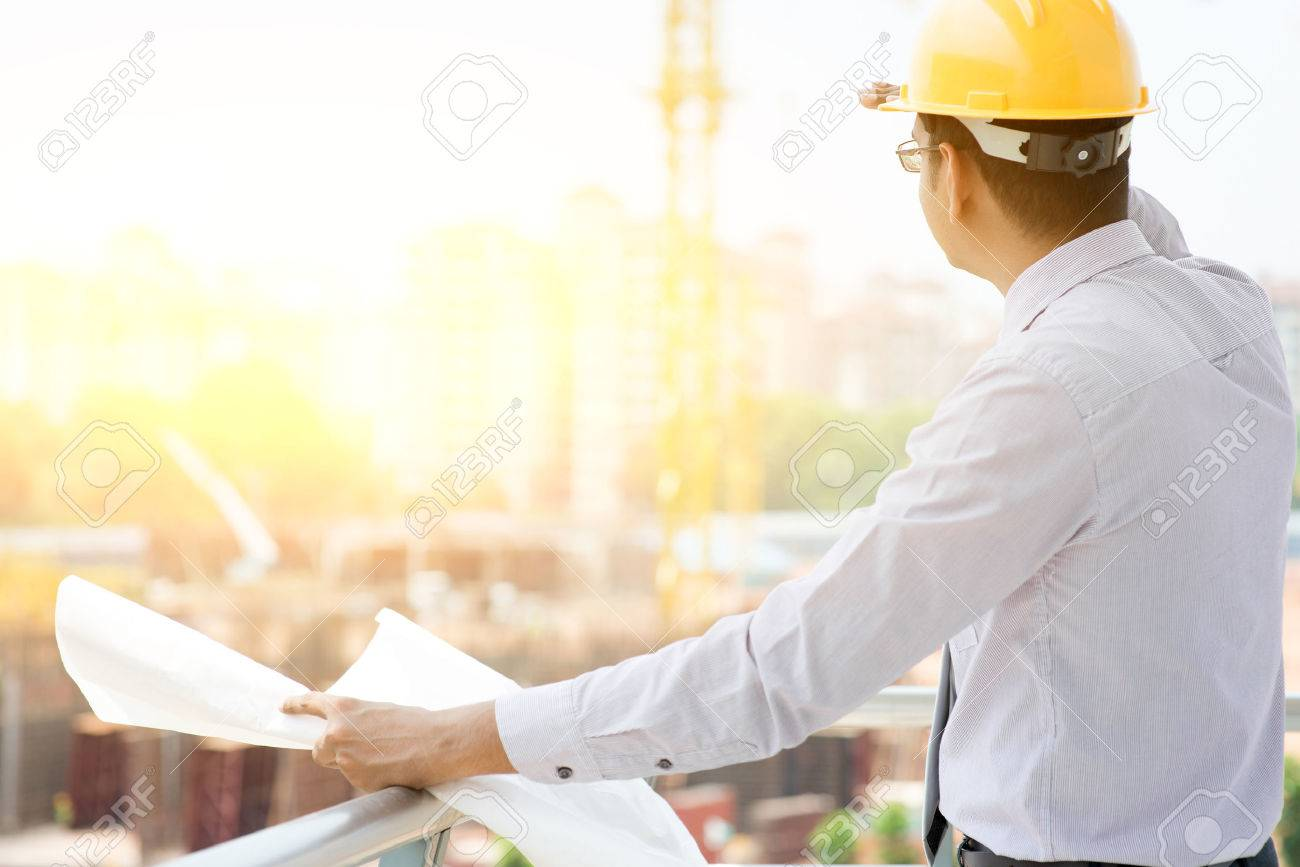 c5eb0b287ec Asian Indian male site contractor engineer with hard hat holding blue print  paper looking away inspecting