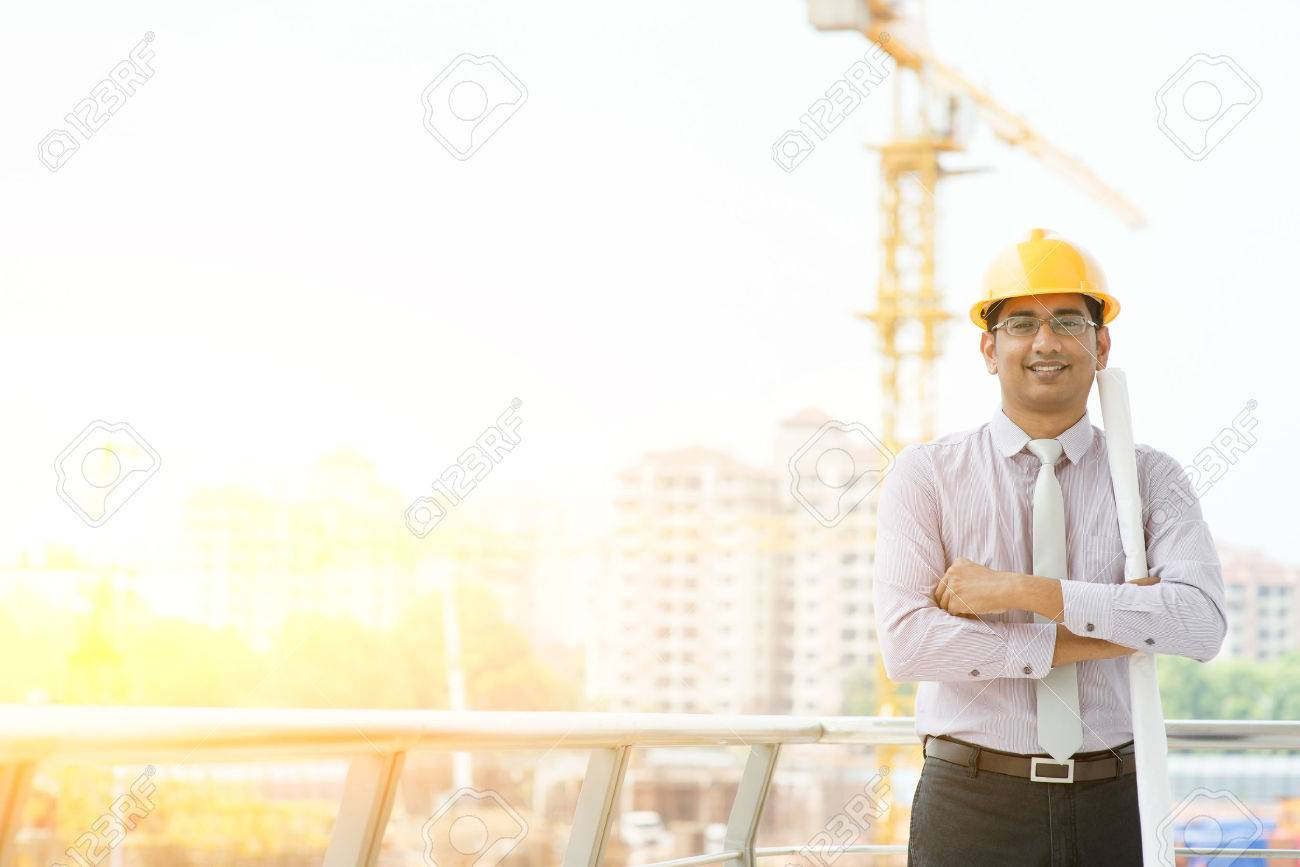 c25209a7ab0 Portrait of Asian Indian male site contractor engineer with hard hat  holding blue print paper looking