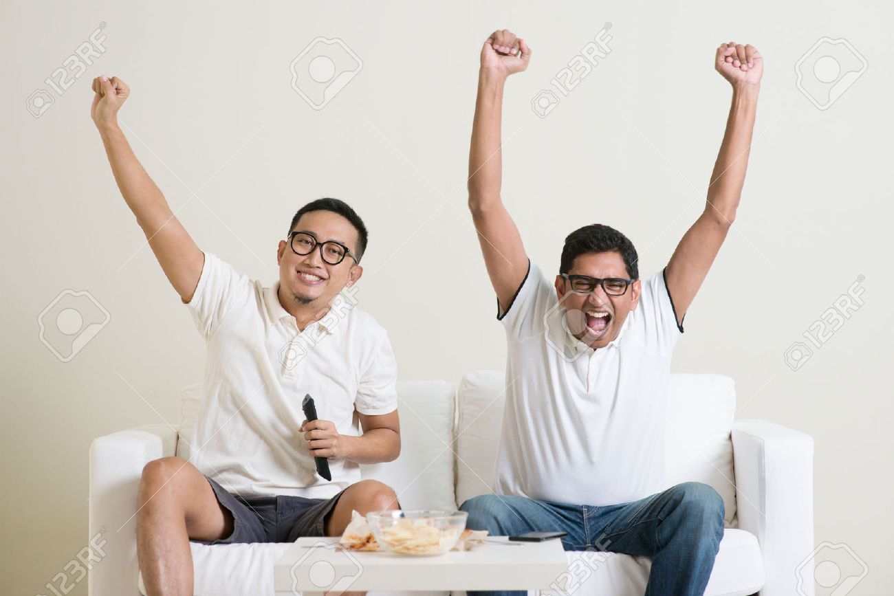 Cheerful group of friends watching football game on tv at home. - 50680663