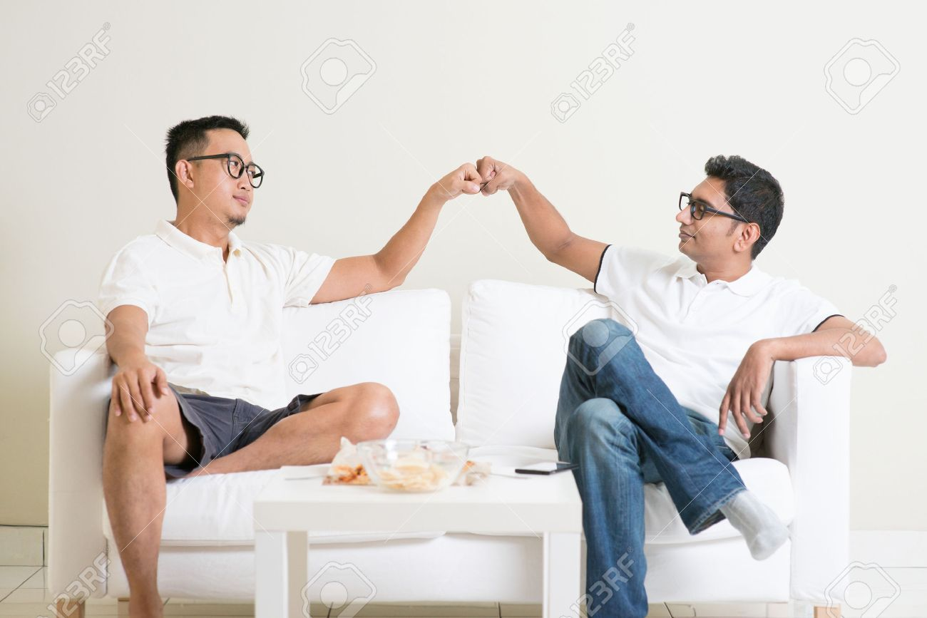 Man sitting on sofa and giving fist bump to friend at home. Multiracial people friendship. - 50680693