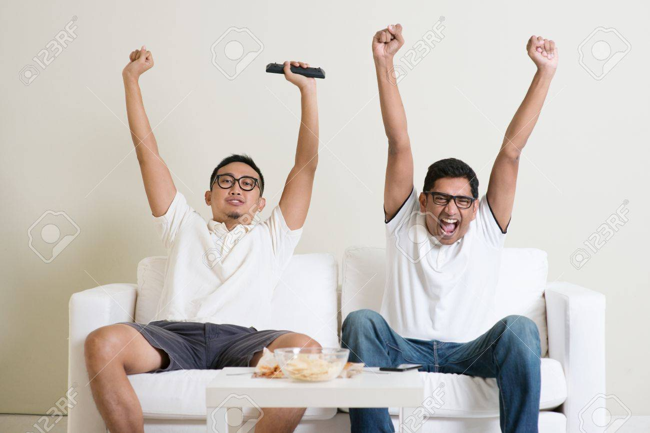 Friendship, technology and home concept. Happy male friends with remote control and junk food at home. - 50680694