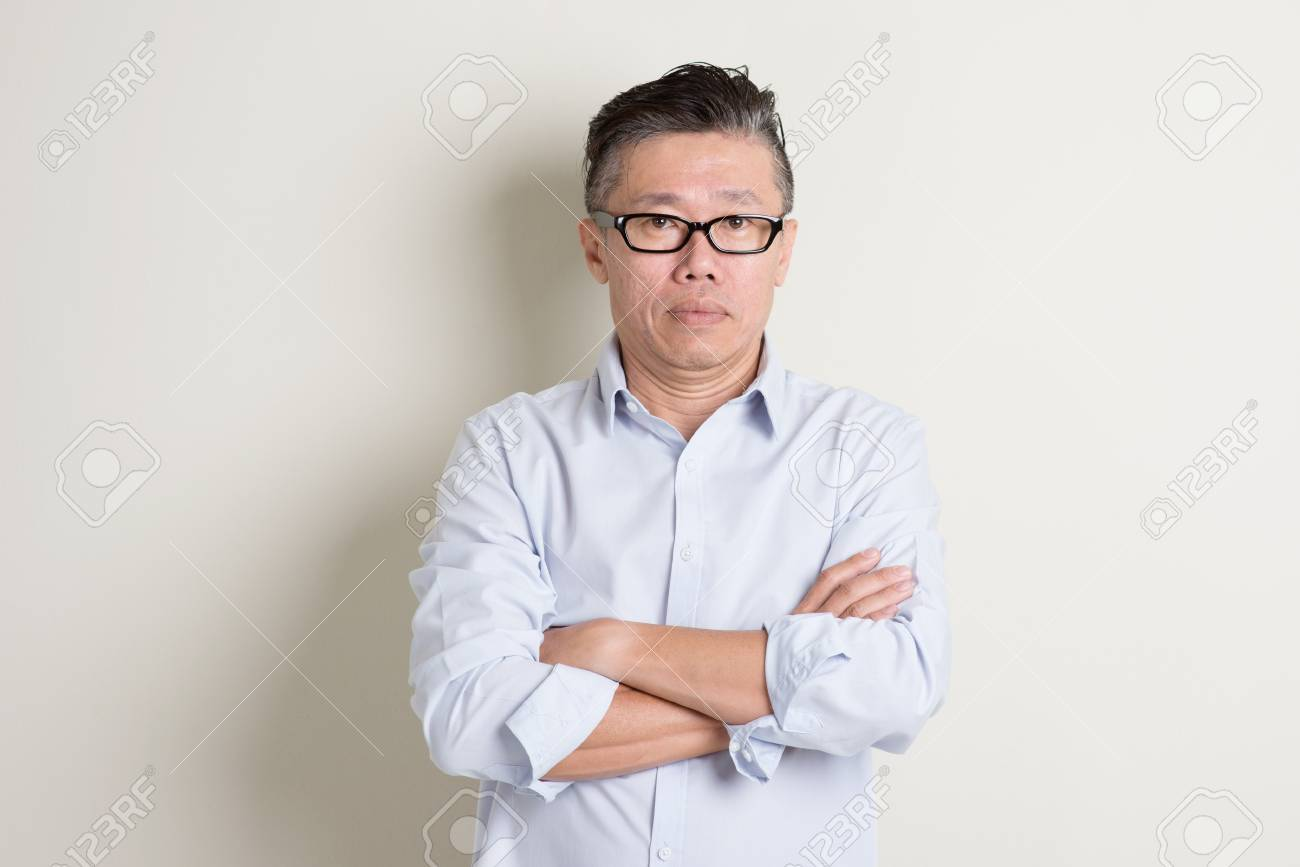 Portrait of single mature 50s Asian man in casual business arms crossed and standing over plain background with shadow. - 51835747