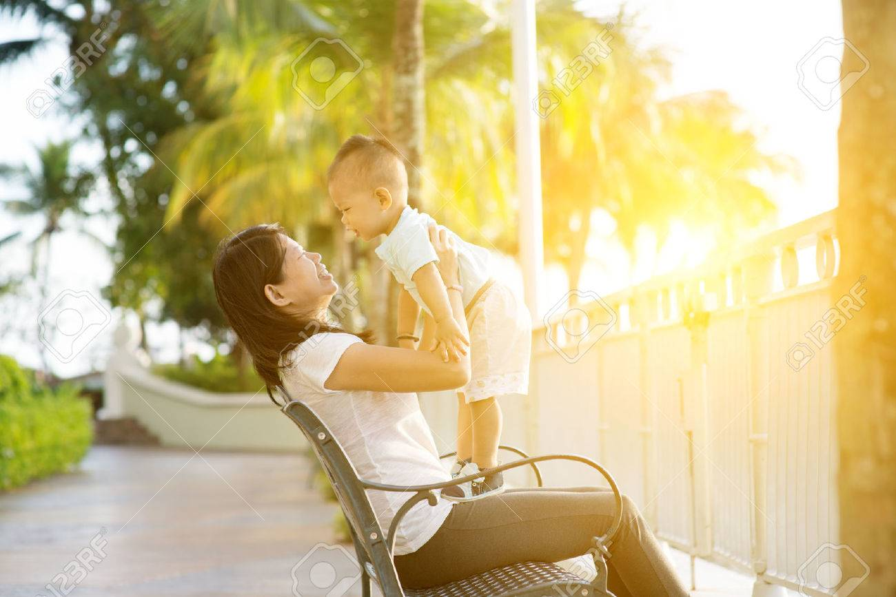 Mother and son having fun at outdoor in sunset during holidays. - 52944245