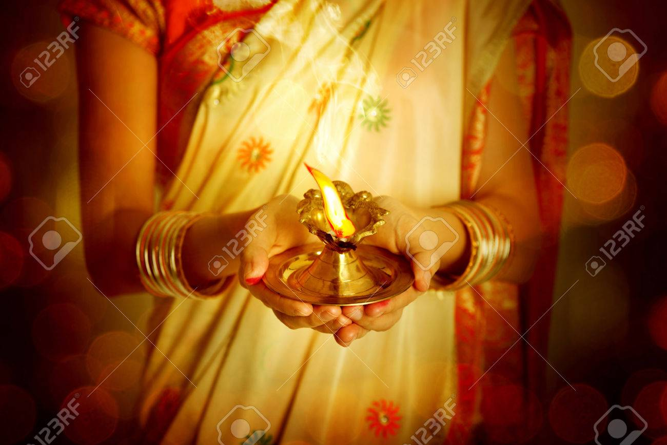 Close up Indian woman in traditional sari lighting oil lamp and celebrating Diwali or deepavali, fesitval of lights at temple. Female hands holding oil lamp. - 64805570