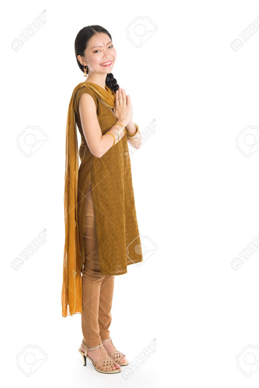 e39ae53018 Stock Photo - Young mixed race Indian Chinese girl in traditional punjabi  dress greeting, full length standing isolated on white background.