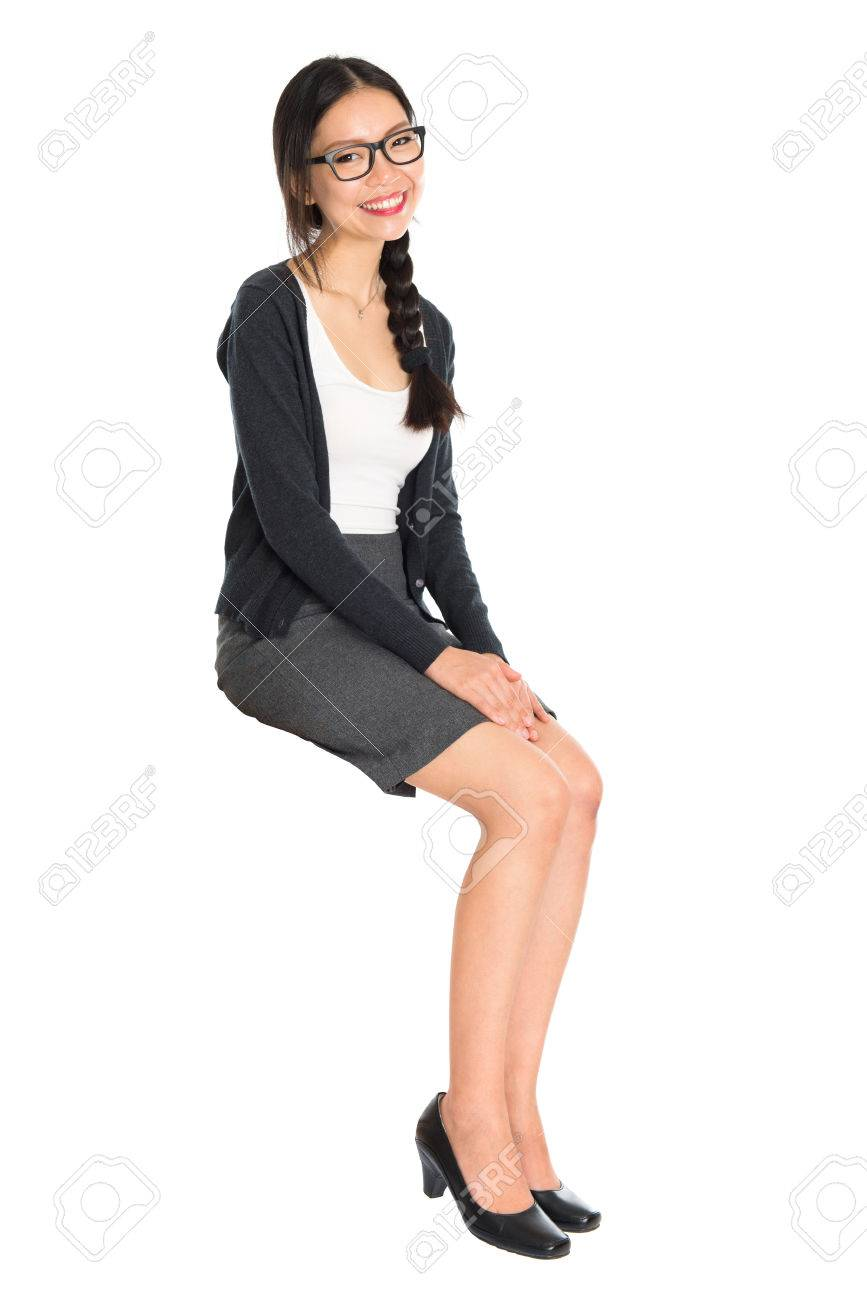 Full body portrait of young Asian woman sitting on invisible chair, isolated on white background. - 64805870