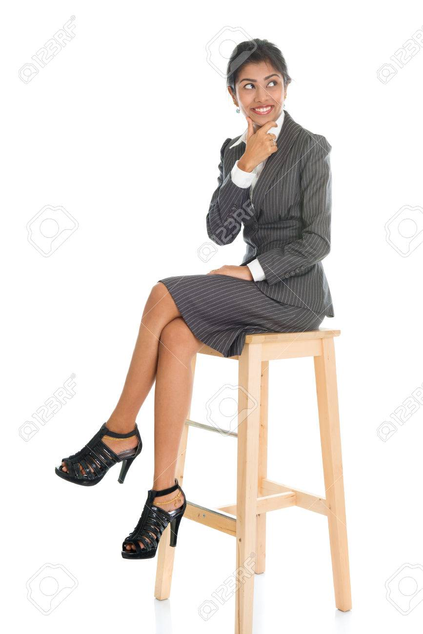 Full length black businesswoman sitting on high chair and having a thought, isolated on white background. - 66020269