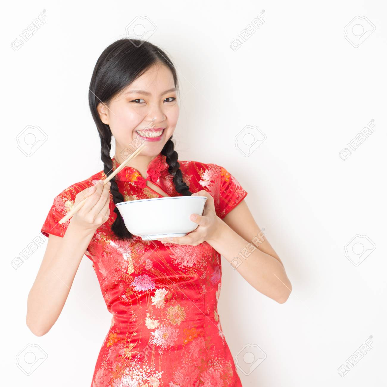 fa456479f Portrait of young Asian woman in traditional qipao dress eating, hand  holding bowl and chopsticks