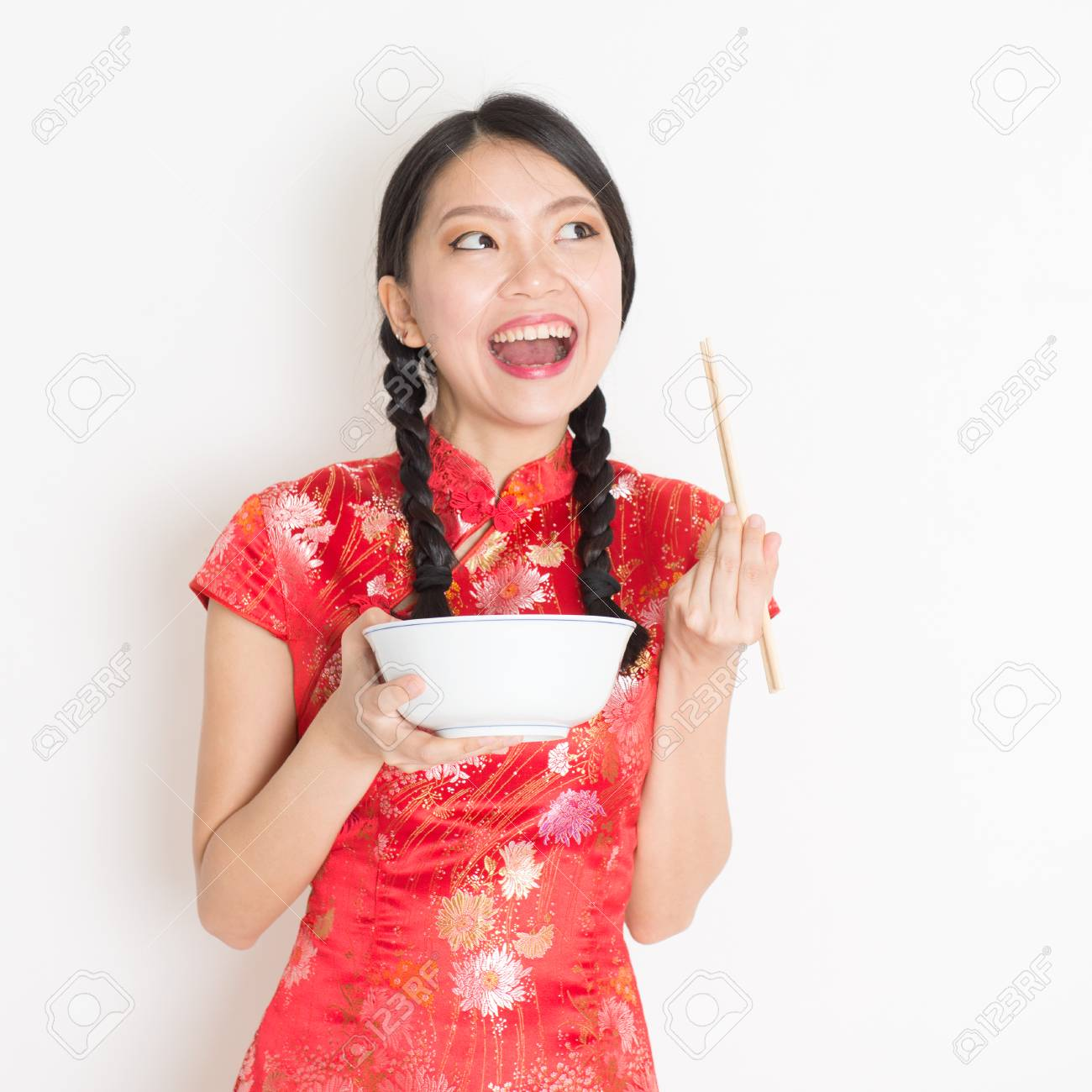 deec26f8d Portrait of young Asian woman in traditional cheongsam dress eating, hand  holding bowl and chopsticks