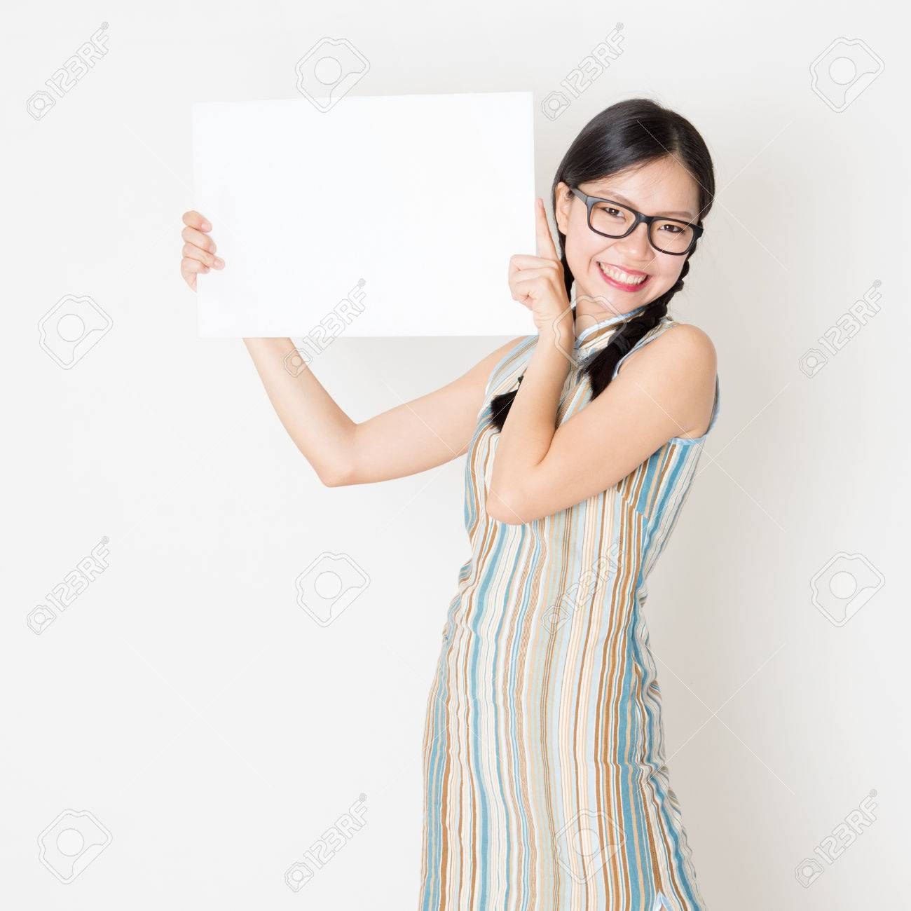 933e4bc94 Portrait of young Asian girl in traditional qipao dress hand holding white  blank paper card,