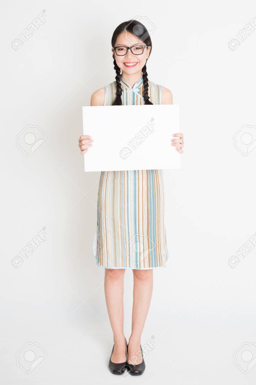 Retrato De Joven Mujer Asiática En El Vestido De Qipao Tradicional Mano Que  Sostiene Una Tarjeta De Papel En Blanco Blanco c3f3ce34a58c