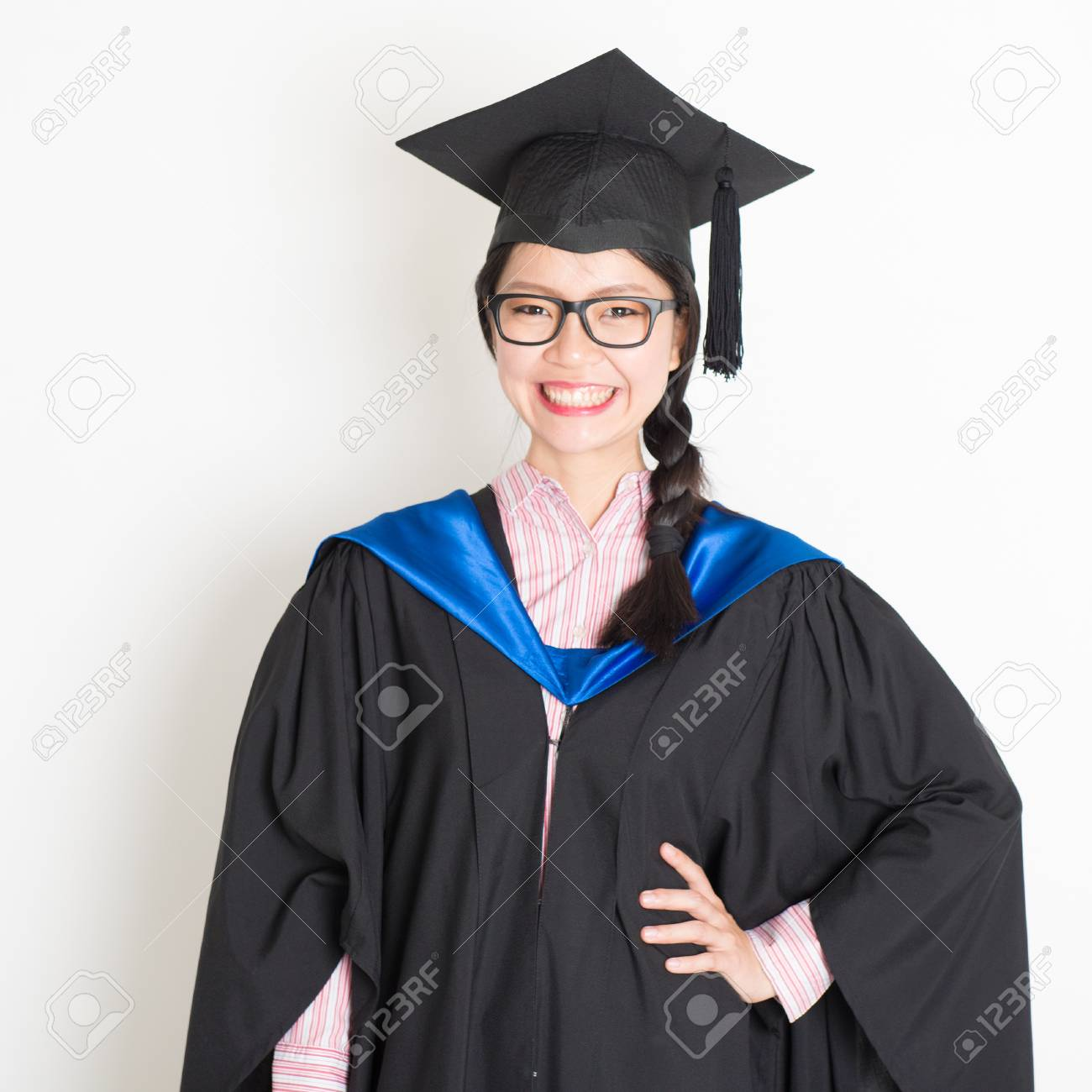 49e516df937 Stock Photo - University student in graduation gown and cap. Portrait of  east Asian female model standing on plain background.