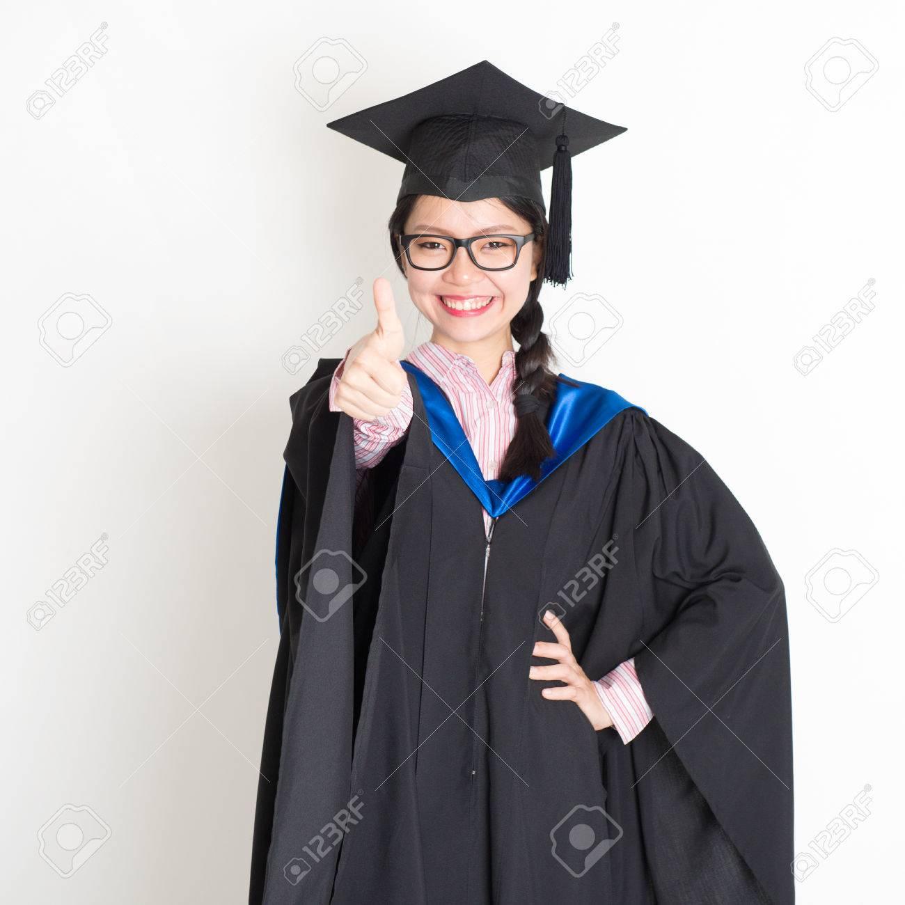 Estudiante De La Universidad En El Vestido De La Graduación Y La Tapa Que Da El Pulgar Para Arriba Firma Retrato De La Posición Femenina Asiática Del