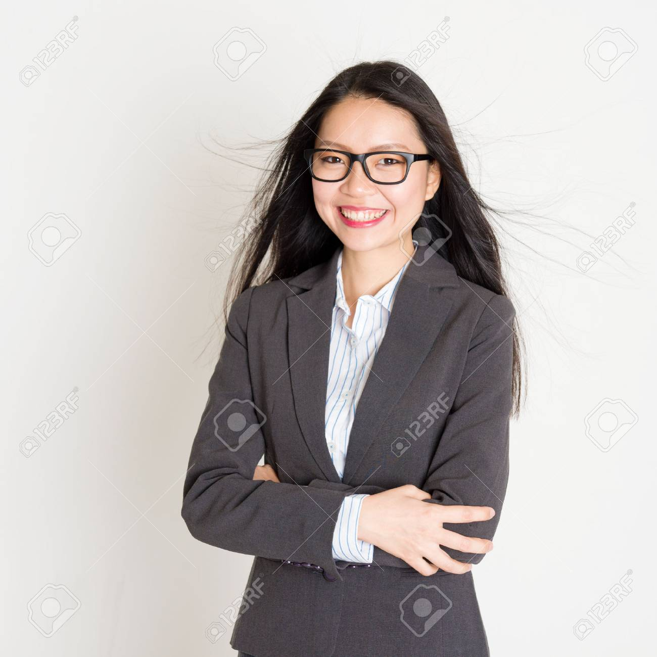 Portrait of young Asian businesswoman in formalwear smiling and looking at camera, standing on plain background. - 70286186