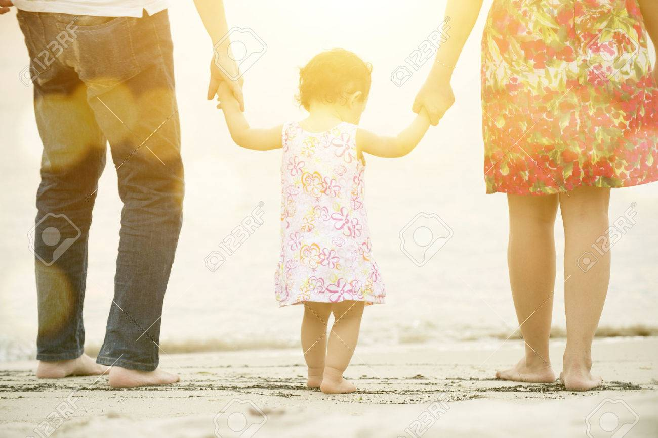 Happy Asian family outdoor activity, holding hands together walking on sand seaside in sunset during vacations. - 70563422