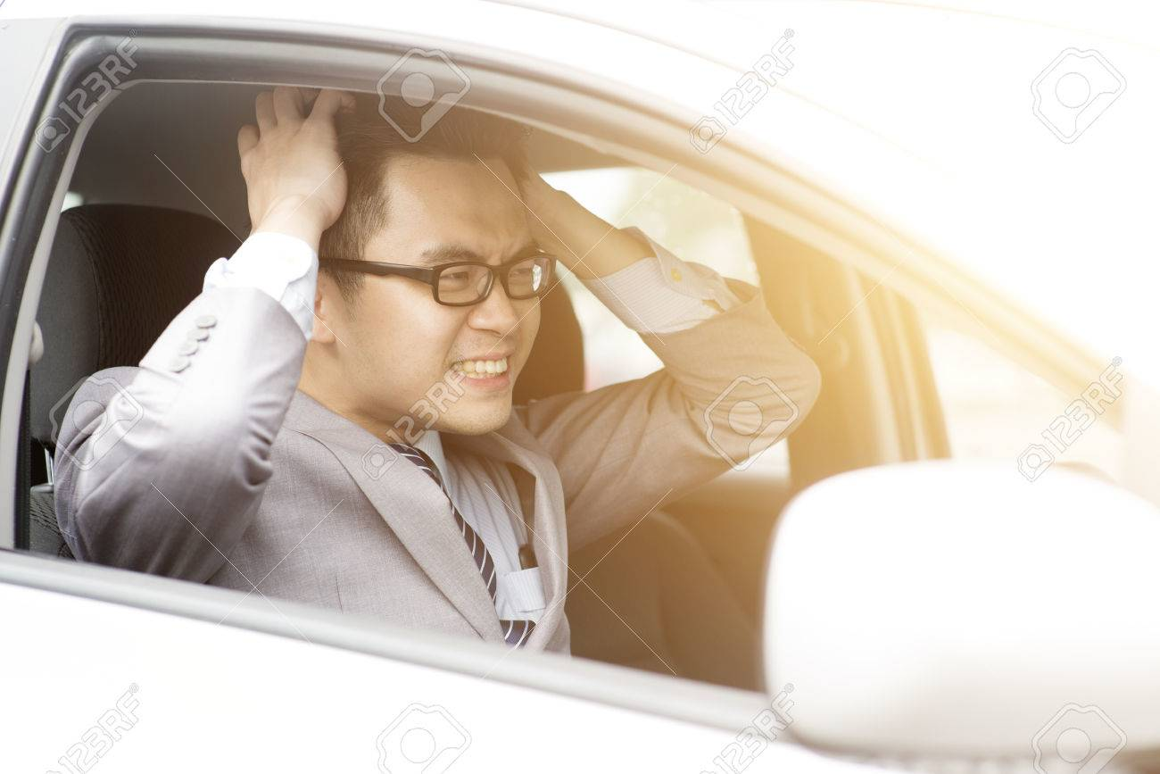 Portrait displeased angry pissed off aggressive Asian business man driving car, shouting at someone in traffic hands grabbing hair. Emotional intelligence concept. Negative human expression. - 74883019
