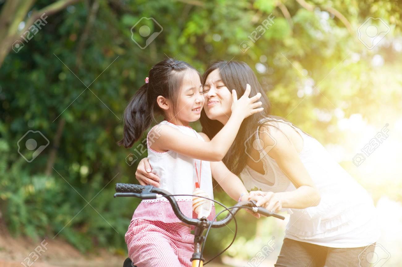 Little girl biking in the park mother giving a goodbye kiss stock little girl biking in the park mother giving a goodbye kiss asian family outdoor stopboris Gallery