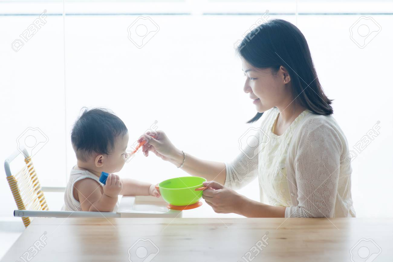 Happy Asian family at home. Mother feeding solid food to 9 months old toddler in the kitchen, living lifestyle indoors. - 97097033