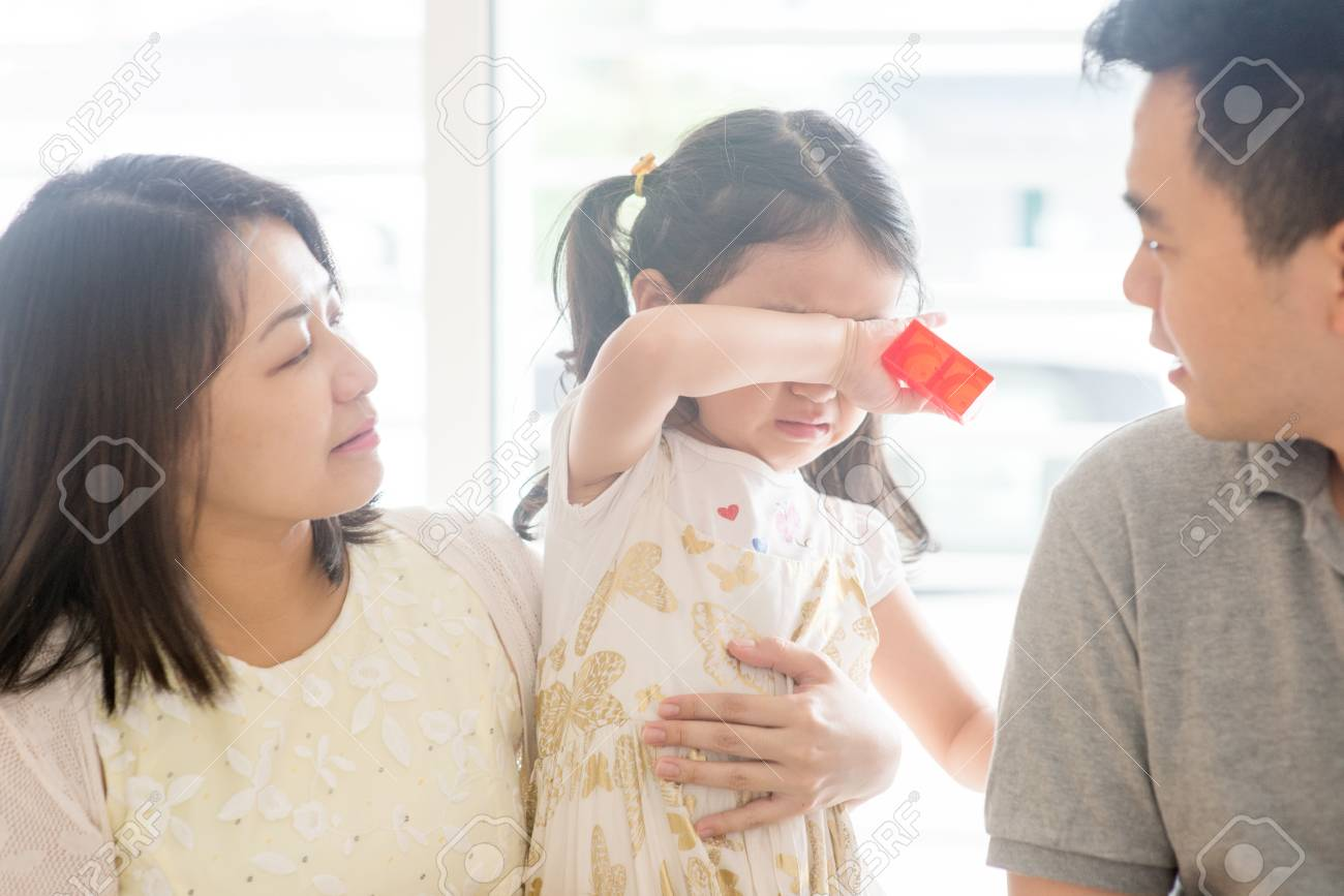 Parents comforting crying daughter. Asian family at home, natural living lifestyle indoors. - 96889850