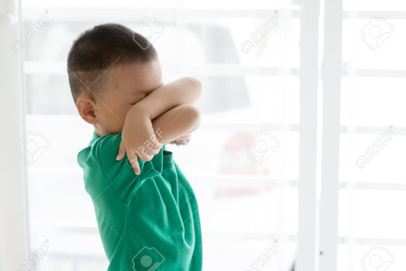 Young child at home. Playful Asian boy covering his face. - 98826249