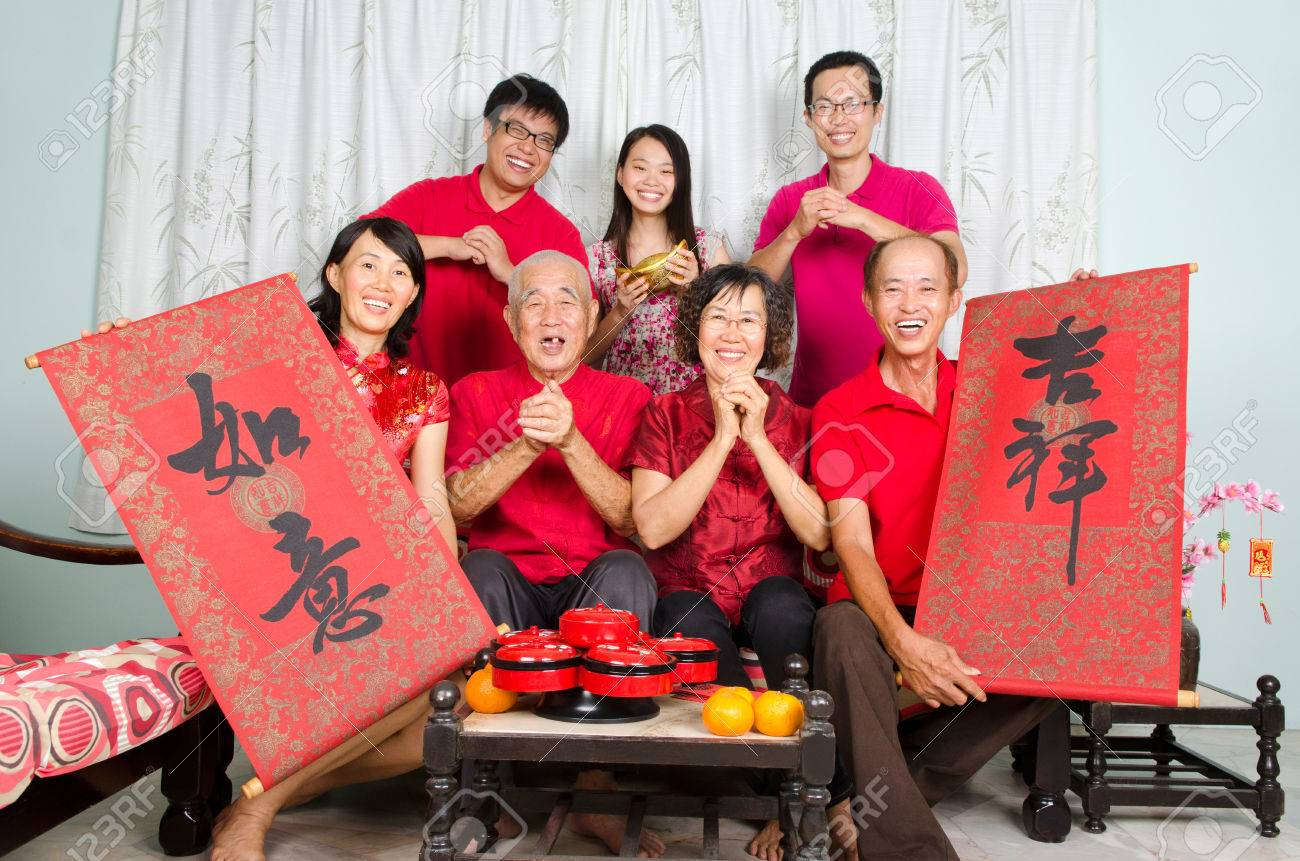"""Asian family celebrate chinese new year, family member hold bunting with the word of """"auspicious"""" and """"wishful"""" in chinese character - 50313015"""