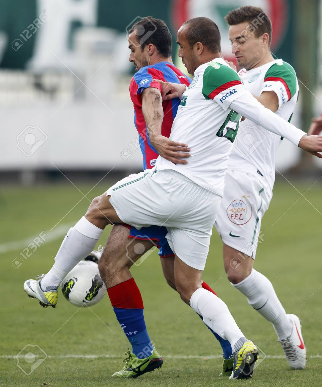 BUDAPEST - March 31: Dajic of Vasas (L) between Junior (M) and Kulcsar (R) of FTC during FTC vs. Vasas Hungarian OTP BANK League football game at Albert Stadium on March 31, 2012 in Budapest, Hungary. Stock Photo - 12935753