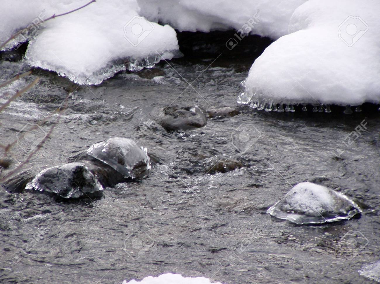 snowy and icy rocks sticking out of the water Stock Photo - 733903