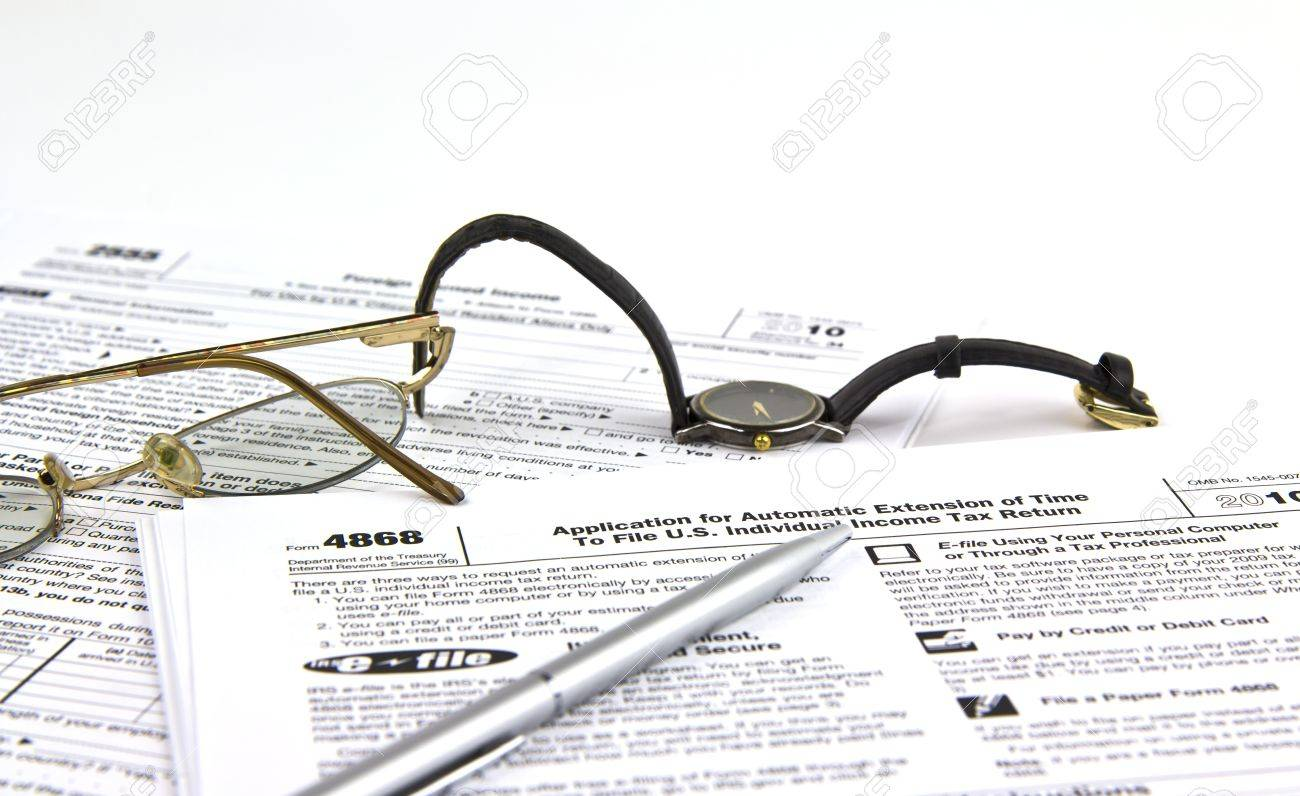 IRS Tax Extension Form (4868) With Pen, Watch And Glass Stock Photo