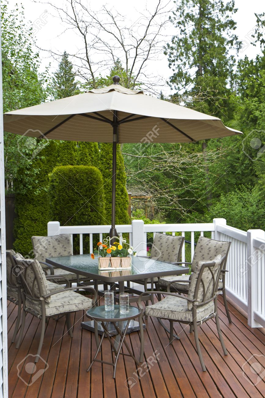 Cedar Wood Outdoor Patio, Glass Table, Chairs, Sun Umbrella And  Refreshments Stock Photo