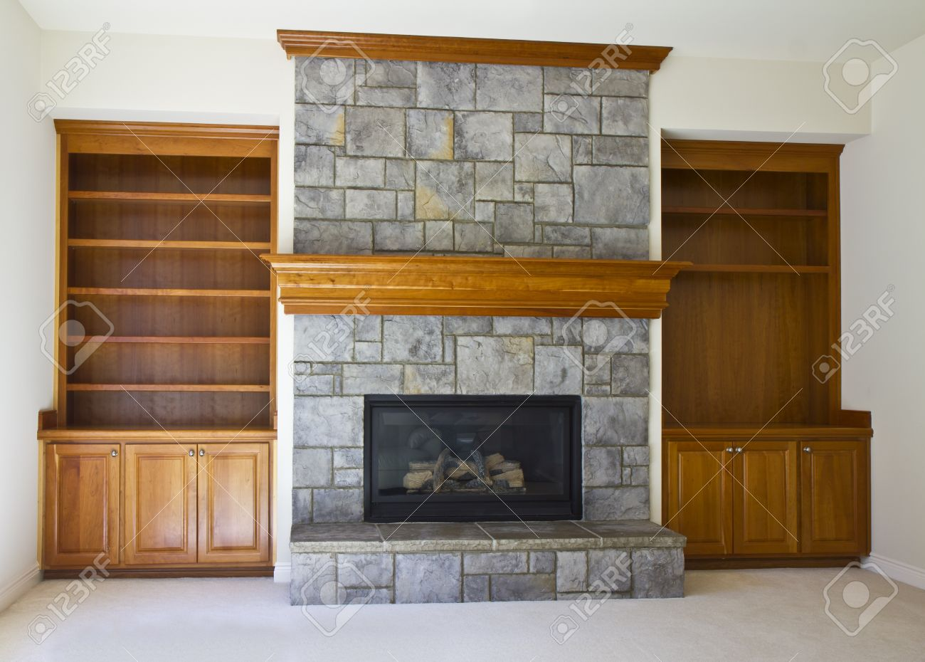stone fireplace with book shelves on white wall stock photo
